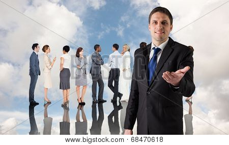 Handsome businessman holding hand out against blue sky with white clouds and business people