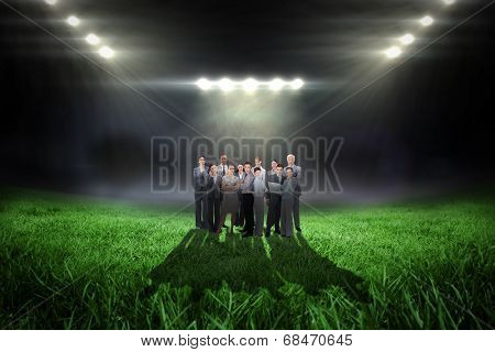 Business team looking at camera against football pitch with bright lights