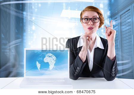 Thinking redhead businesswoman with laptop showing graphic