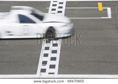 Race car crossing the finishline on the straight strech of a circuit on the grid