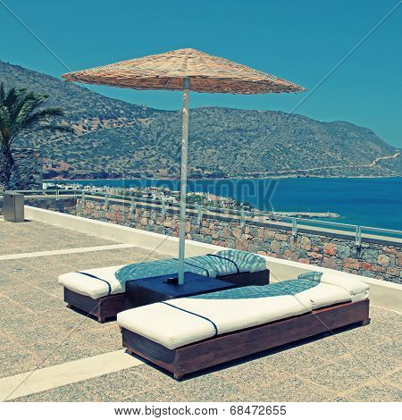 Sun Beds And Umbrellas On Terrace In Summer Resort