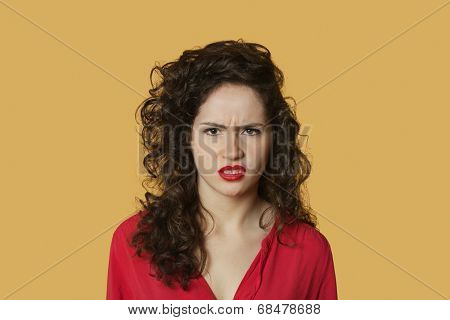 Portrait of angry young woman frowning over colored background
