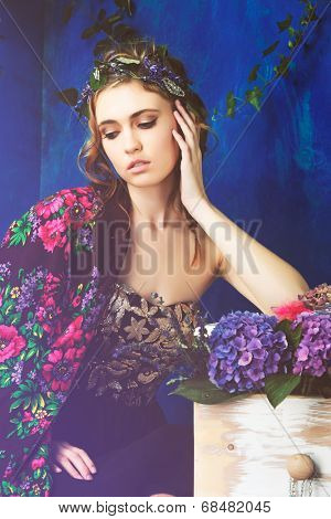 Beautiful brunette woman with braid hairstyle and natural makeup. Wearing black bohemian sequin corset dress. Against blue grunge background. Wearing flowers in her hairstyle