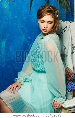 portrait of a beautiful woman with red hair in curly braided hairstyle. wearing a romantic blue turquoise dress on grunge blue background