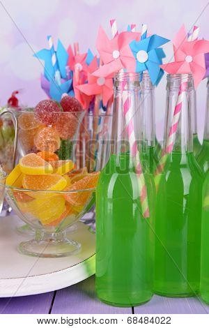 Bottles with drink and sweets on table on bright background
