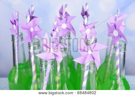 Bottles of drink with straw on bright background