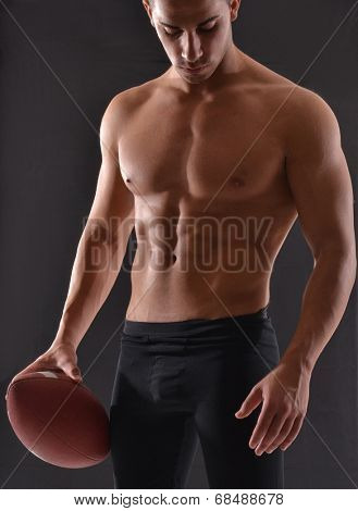 Shirtless rugby player on black background.