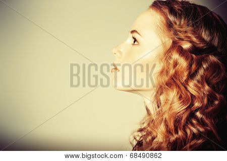 Portrait of a beautiful girl standing in profile. Beauty, fashion, hairstyle.