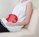 image of menstruation  - woman using hot pack to relieve abdominal pain from menstruation - JPG
