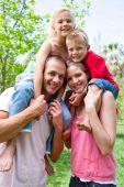 foto of summer fun  - Happy parents giving their children piggy - JPG