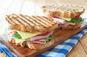stock photo of deli  - Grilled sandwiches with ham and cheese on top of a chopping board