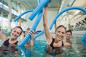 picture of day care center  - Happy fitness class doing aqua aerobics with foam rollers in swimming pool at the leisure centre - JPG