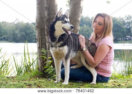 Young Woman Petting Her Husky Dog