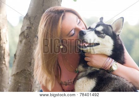 Young Woman Hugging With Her Husky Dog