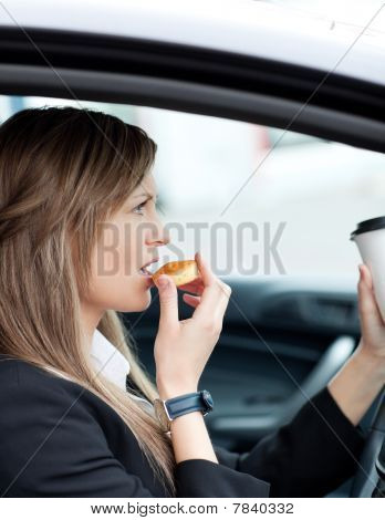 Attractive Businesswoman Eating And Holding A Drinking Cup While Driving