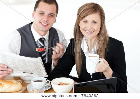Young Couple Of Business People Reading A Newspaper While Having Breakfast