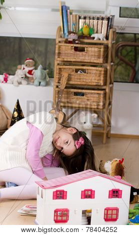 Girl Playing With Dolls House
