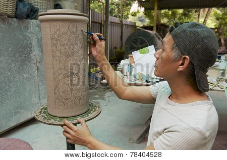 Man paints traditional tribal tattoo motives decoration, Kuching, Malaysia.