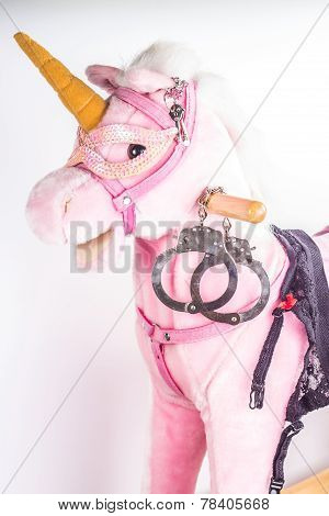 Pink unicorn toy with handcuffs on white background. Sexual symbols.