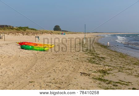 Brightly coloured canoes Studland knoll beach Dorset England UK