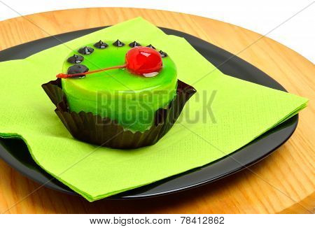 Delicious Green Cake With Cherry On Black Plate On Cutting Background
