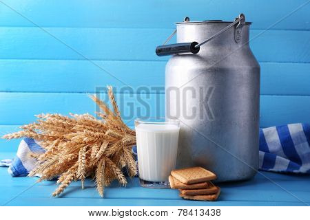 Retro can for milk, milk glass, cookie and sheaf on color wooden background