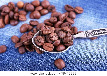 Spoon with coffee beans on ripped jeans background