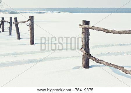 Old fence in snow on a sunny day