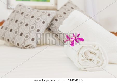 fresh flower and towel on bed, hotel room bedroom interior