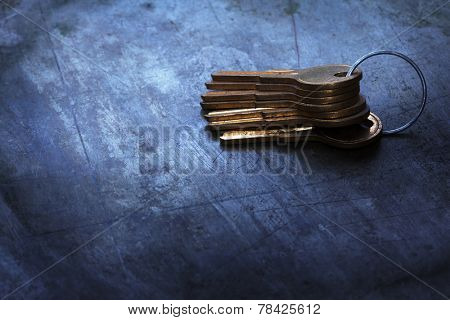Stacked Brass keys on a bluish old metal background.