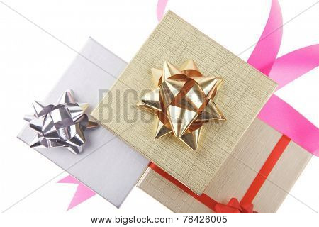 silver and gold gift boxes with pink bow isolated over white background