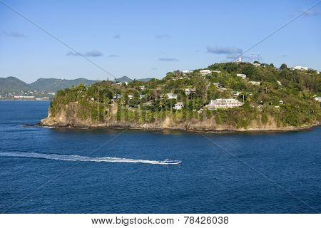 speedboat going past oceanfront homes on the island of St Lucia