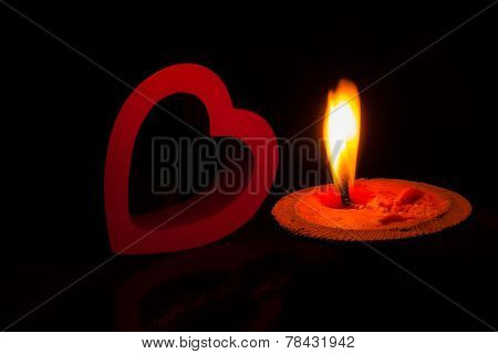 A Burning Candle And Red Heart In Dark.