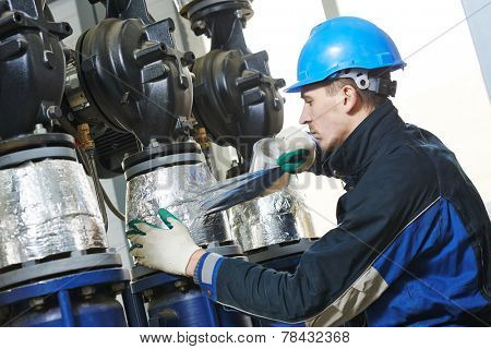 industrial construction worker at boiler room pipe heat insulation work