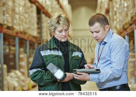 manager and worker in warehouse with bar code scanner