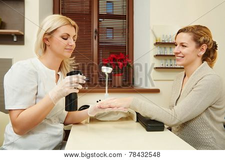 Manicurist with client perfoming hand nail protection and care in beauty salon