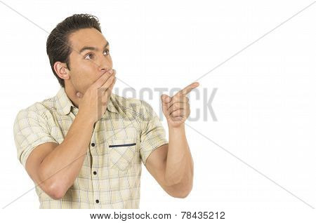 young handsome hispanic man posing pointing at something funny