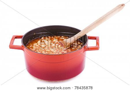 Haricot bean cooked in cast iron cooking pot with wooden spoon isolated on white background.