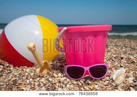 Child's Bucket, Ball And Other Toys On Tropical Beach Against Blue Sky