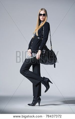 full-length fashion model in fashion dress with handbag posing on gray background