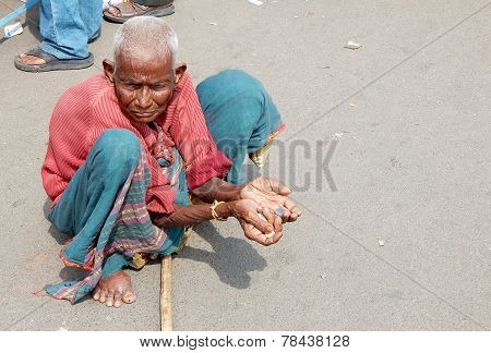 Poor Indian woman seeking help on a busy road
