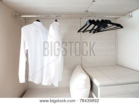 White Shirts Hanging On Built-in Cloths Racks, With Drawers And Other Accessories