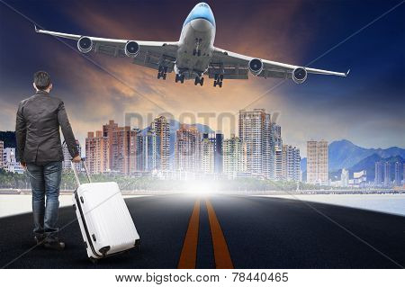 Young Man With Belonging Luggage Standing  Against Urban Scen And Passenger Jet Plane Flying Over Sk