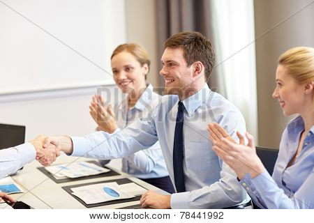 business, people and partnership concept - smiling business team shaking hands and applauding in office