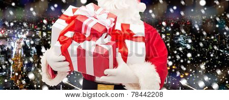 christmas, holidays and people concept - close up of santa claus with gift box over snowy night city background