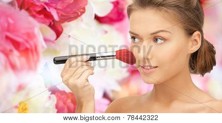 beauty, people and accessories concept - beautiful smiling woman with bare shoulders and make up brush over pink floral background