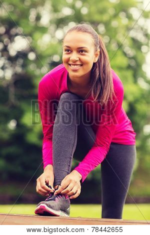 sport, exercise, park and lifestyle concept - smiling african american woman exercising outdoors