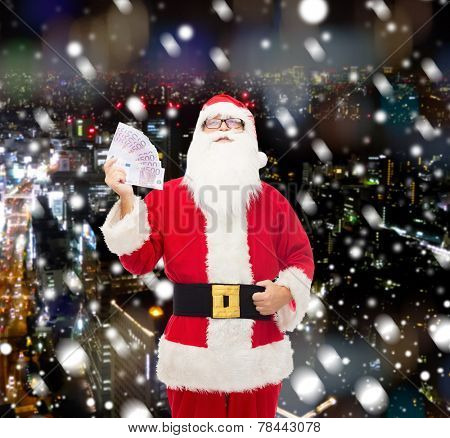 christmas, holidays, winning, currency and people concept - man in costume of santa claus with euro money over snowy night city background