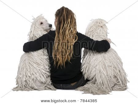 Rear View Of Two White Corded Standard Poodles And A Girl With Dreadlocks Sitting In Front Of White