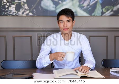 Relaxed young man drinking coffee at home, sitting on coffee shop